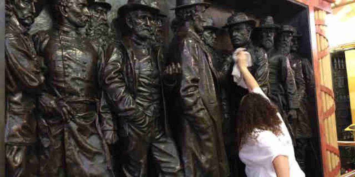 Volunteers dust and clean Soldiers and Sailors Monument