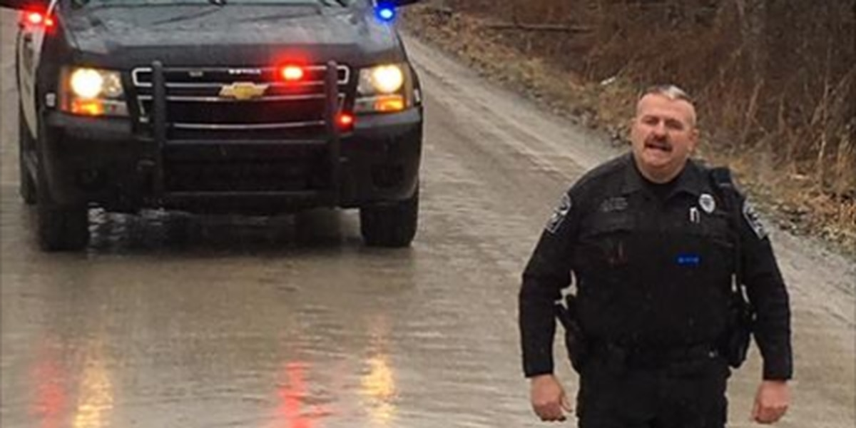 Police officer stands in one of the biggest potholes you will ever see